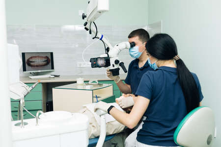 Medical Stomatology Concept. Doctor making teeth examination research survey using microscope in dentistry. Dentist is treating patient in modern dental office