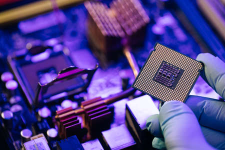 Engineer showing a computer microchip on motherboard background. Electronic circuit board with processor Standard-Bild