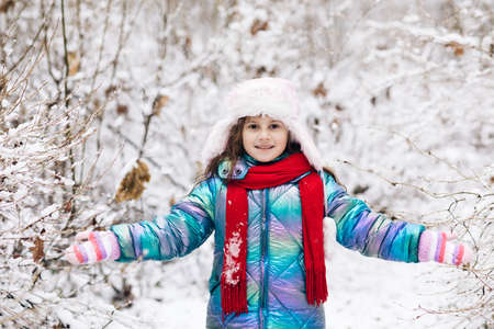 Happy child girl playing with snow on snowy winter walk. Happy winter time. Happy winter moments of joyful young girl with long brunette hair, winter clothes having fun in snowing time