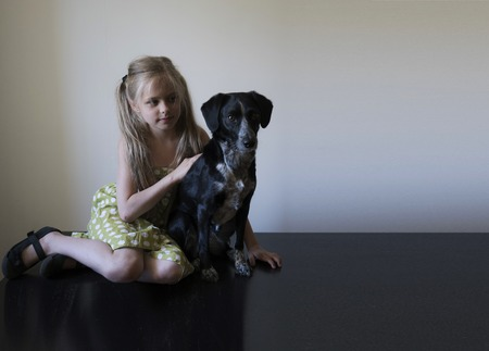 shiny floor: girl with her dog sitting on a shiny black floor against a white wall