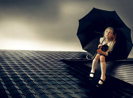 blond hair: rain on the roof and beautiful girl with blond hair under an umbrella Stock Photo