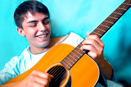 hand jamming: young man relaxing, laughing and playing guitar Stock Photo