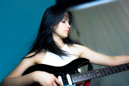 Beautiful brunette girl with a guitar on a blue background