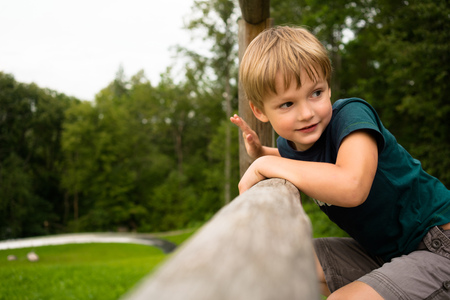 cheerful boy climbs on a wooden hill in the background of summer greens Stock Photo