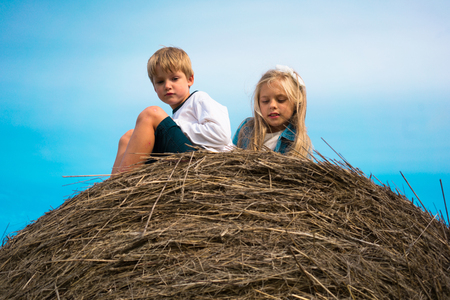 Boy with a girl sitting on a haystack on the background of the sky