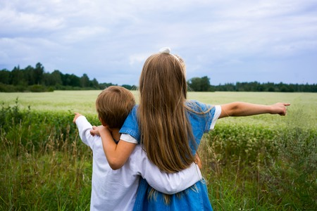 boy and girl on the background of summer field