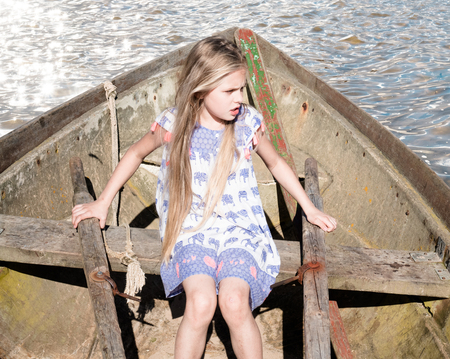 old boat: girl sitting in an old boat with wooden oars Stock Photo