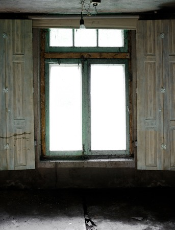 abandoned room: old window with spider webs in an abandoned room. light bulb on the ceiling. vintage