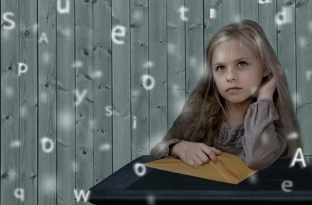 correspondent: vintage children. Cute girl sitting at a table with a large letter envelope