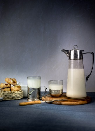 stoop: Milk from a jug pouring into glass on old wooden table. space for text Stock Photo