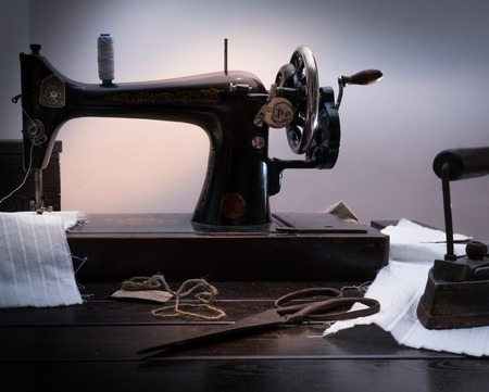 Classic retro style manual sewing machine ready for sewing work, scissors, fabric and old scissors Stock Photo