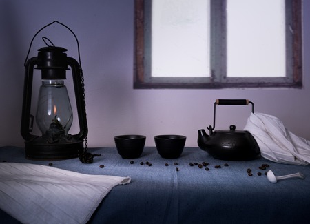 tea lamp: lamp and glasses with black tea on a table in the evening on a background of a window