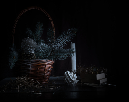 12 month old: christmas. basket with fir branches and cones on a dark background.