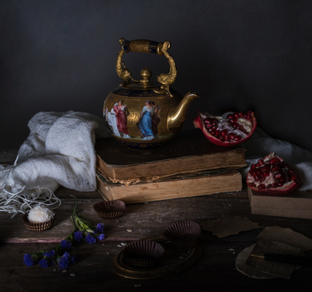 vintage gold with enamel kettle, books and pomegranate on a wooden table. dark background.