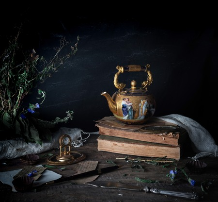 still life. vintage gold with enamel kettle, books and clock on the wooden table. dark background. space for text