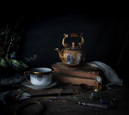 still life. vintage gold with enamel kettle, books and cup on the wooden table. dark background. space for text