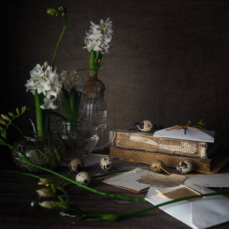 Still life with old books, quail eggs, white hyacinths on a dark background.