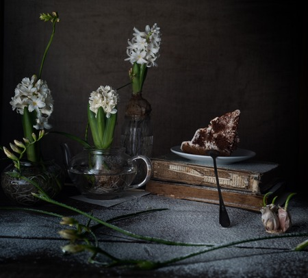 Still life with old books, cake, white hyacinths on a dark background.