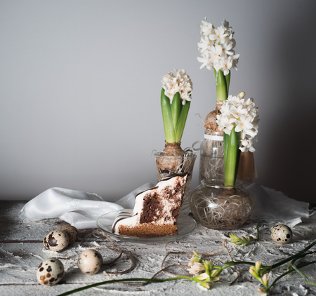 hyacinth in glass vases, cake and quail eggs on a wooden table .