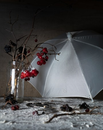 viburnum branches with berries and snow in a transparent vase, umbrella on  wooden table