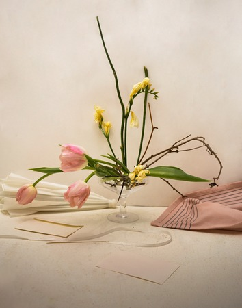 bouquet of pink tulips and yellow freesias in a glass vase on the table with the letters, envelopes, scissors