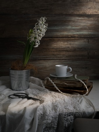 Still life with hyacinth, cup of coffee, old books, scissors on a background of rough wooden walls. vintage. Zdjęcie Seryjne