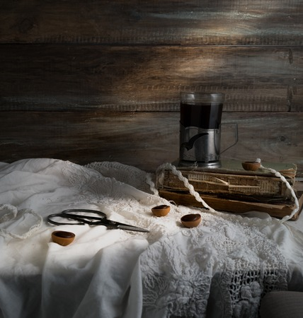 Still life with cup of coffee, old books, scissors on a background of rough wooden walls. vintage Zdjęcie Seryjne