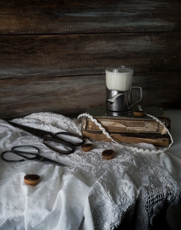 Still life with old books, scissors and a glass of milk on a background of rough wooden walls. vintage
