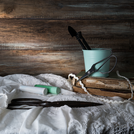 still life with scissors, crayons and lace on a background of rough wooden walls. vintage