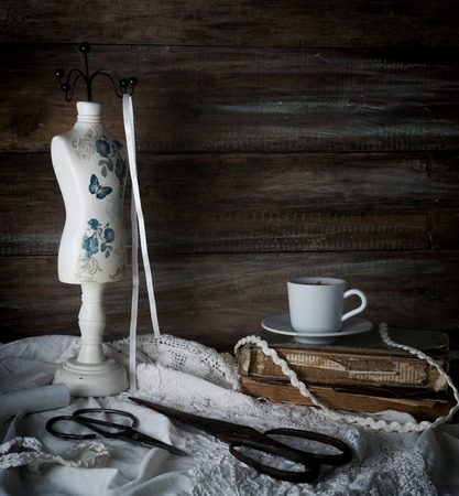 still-life with a cup of coffee, scissors, mannequin sewing and lace on a background of rough wooden walls. vintage Zdjęcie Seryjne