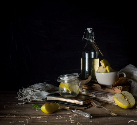 still life with apples, apple juice, old books and a silver knife on a wooden table on a dark background. vintage