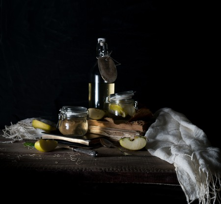 staging: still life with apples, apple juice, old books and a silver knife on a wooden table on a dark background. vintage