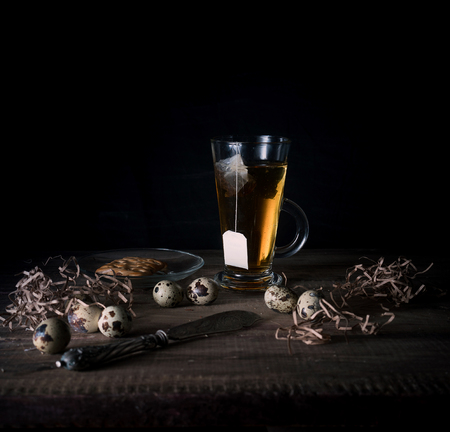 rustic still life. cup of tea and quail eggs on a wooden table. black background