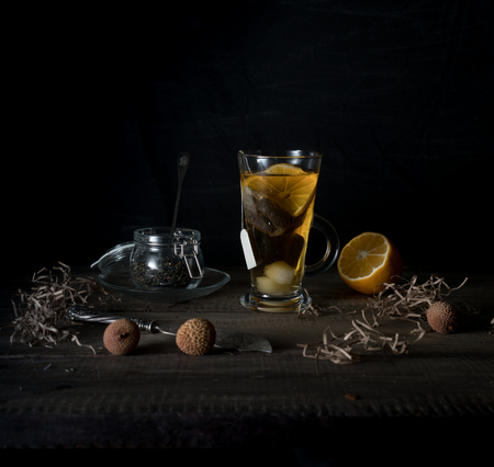 rustic still life. cup of tea, lemon and quail eggs on a wooden table. black background