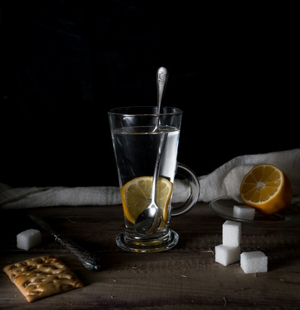 rustic still life. Tea with lemon in a large circle on the wooden table. black background