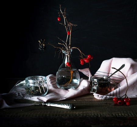 rustic still life. branch viburnum, tea in a big circle and jars on a wooden table. black background