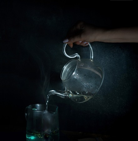 womans hand pours boiling water into a glass kettle. dark background. vintage.