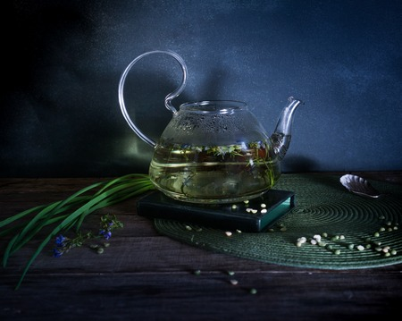 Boiling water and grass in a glass teapot. Dark background. Vintage. Stockfoto