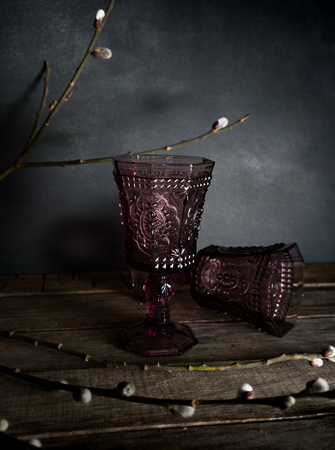 Two vintage glasses on a wooden table, willow branches. Dark background