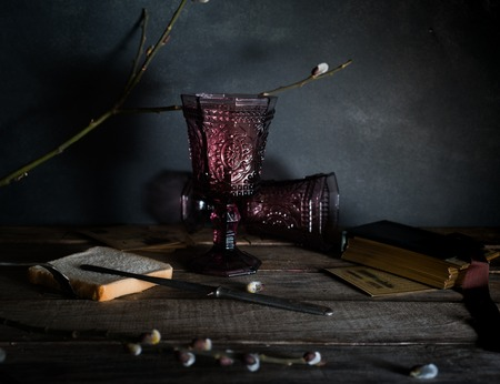 Two vintage glasses on a wooden table, willow branches. Dark background. Stockfoto