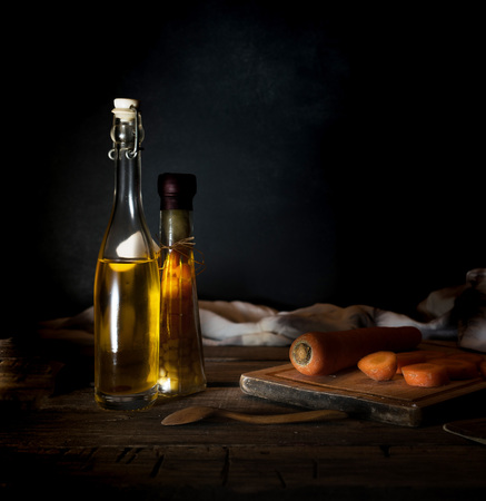 Bottles with oil, herbs and spices at wooden table on black background.