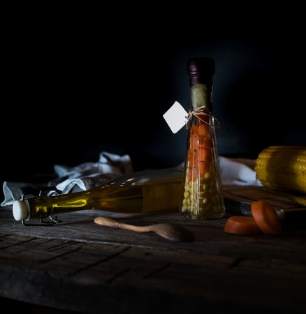 bottle of canned carrots and corn, spices on a wooden table. Dark background