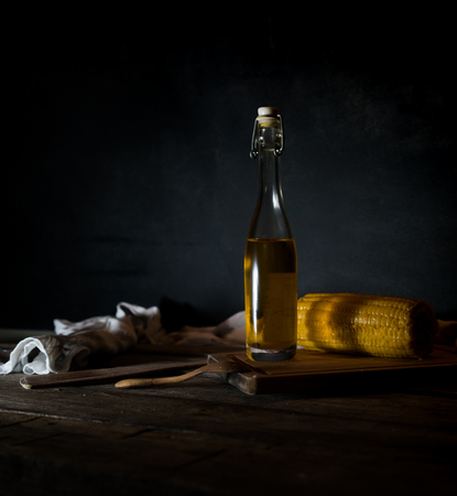 Bottles with oil, herbs and spices at wooden table on black background