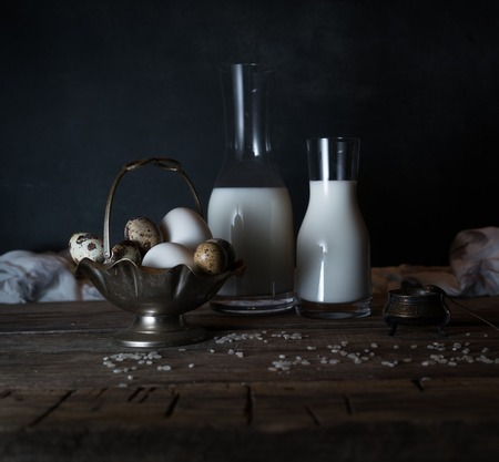 Fresh organic eggs, milk and butter, still life in rustic style, vintage wooden background. Zdjęcie Seryjne