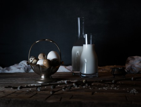 Fresh organic eggs, milk and butter, still life in rustic style, vintage wooden background. Stock Photo