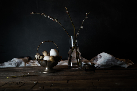 Branches of pussy-willow and quail eggs on a wooden table. Dark background.