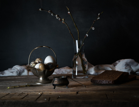 Branches of pussy-willow and quail eggs on a wooden table. Dark background