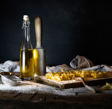Pasta, olive oil on a wooden table. Dark background