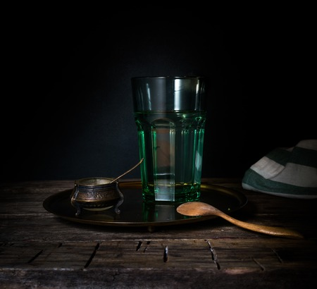 Glass glass with water on a wooden table. Dark background
