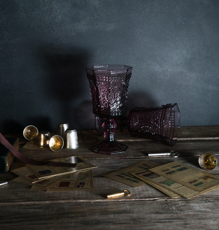 Cards. Two vintage glasses on a wooden table, willow branches. Dark background.
